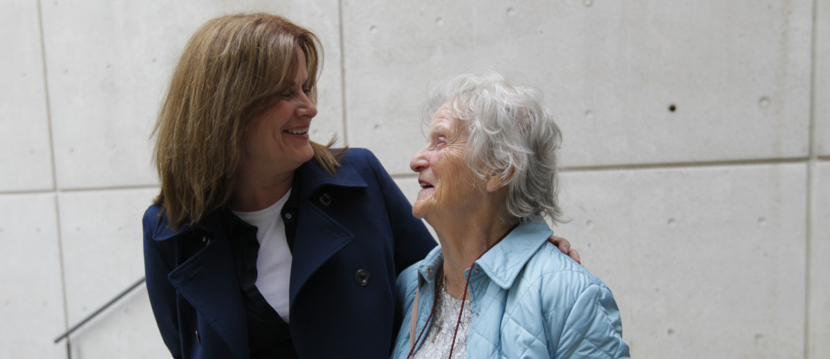 An older and younger woman smiling at each other