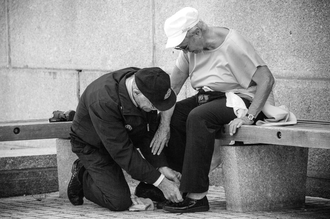 Man looking tying woman's shoelace