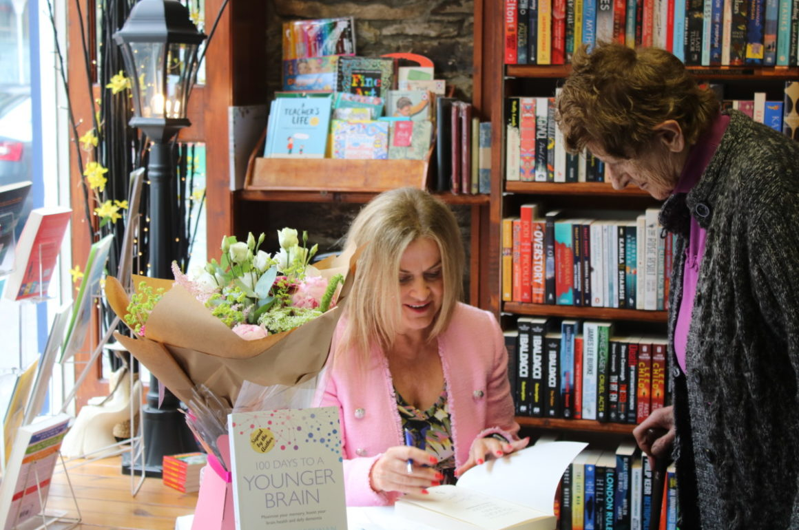 woman signing book for another woman