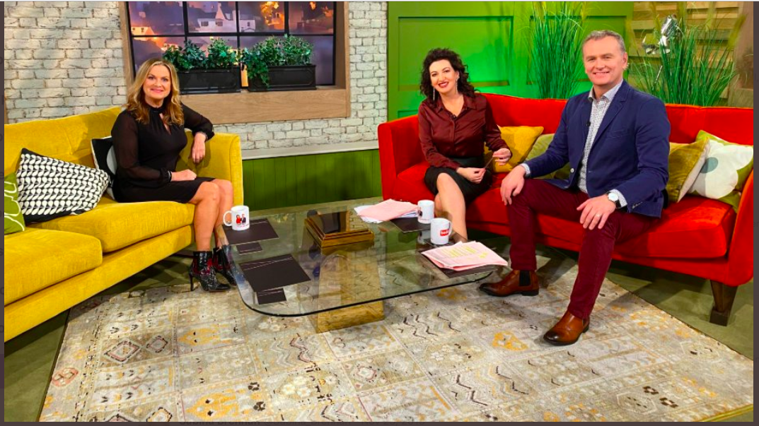 photo of woman on sofa in TV studio with a man and a woman on another sofa